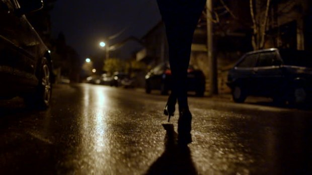 Low angle view point of female legs walking in the dark.
